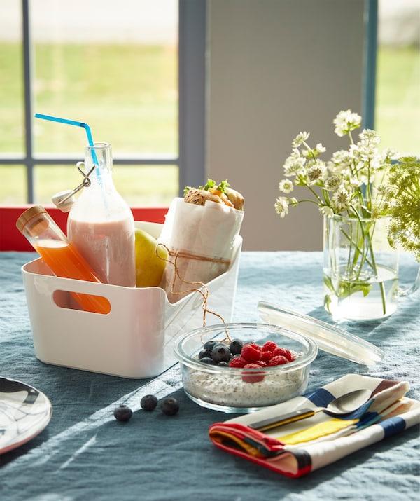Eine VARIERA Box weiß gefüllt mit einem Sandwich, einer Glasflasche mit Jogurt und Saft für ein Frühstück unterwegs.