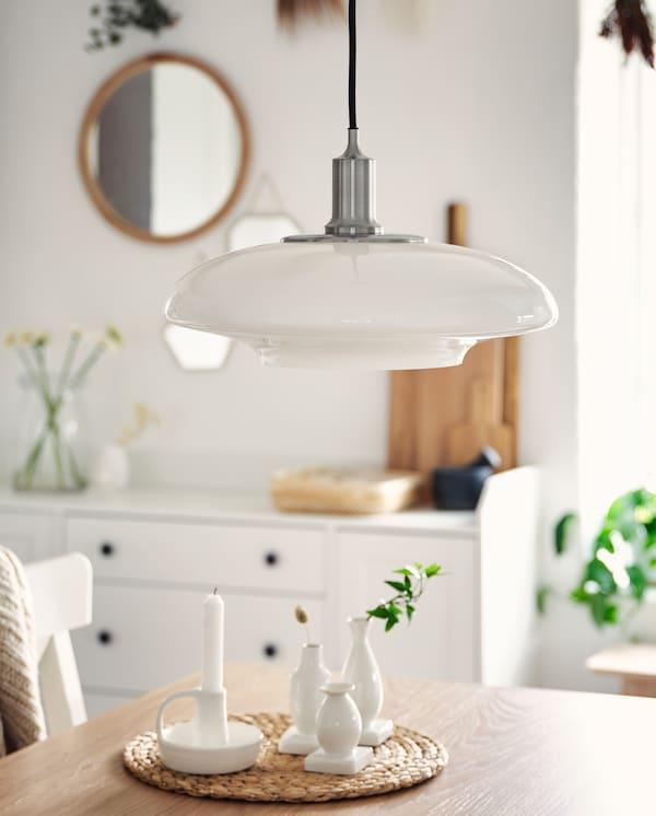Eine vernickelte Hängeleuchte mit einem weißen Leuchtenschirm aus Glas hängt über einer Tischplatte in Eichenfurnier. Auf dem Tisch stehen weiße Vasen.