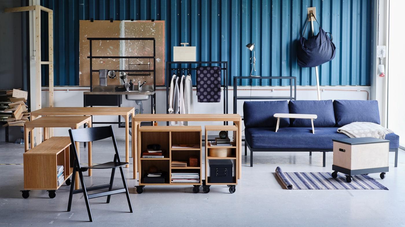 Eine Vielzahl an RÅVAROR Einrichtungsgegenständen, u. a. Tische, ein Tagesbett und Aufbewahrungselemente, steht vor einer blaugrünen Zinkplattenwand.