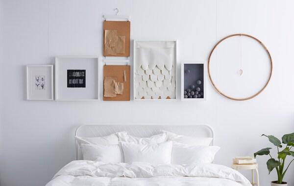 Eine Wand mit Bilderrahmen und verschiedenen Objekten darüber. Alle hängen in einer geraden Linie.