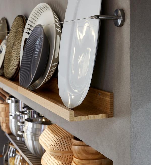 Eine Wand mit dekorativer Aufbewahrung, u. a. mit Tellern auf einer MÅLERÅS Bilderleiste.