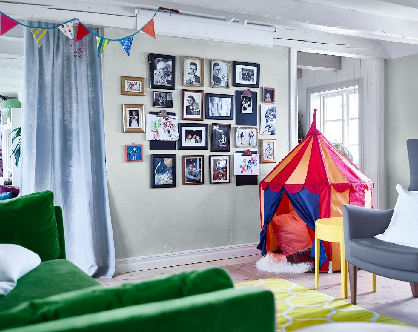 Eine Wand mit Familienfotos vor der ein buntes Zelt für Kinder zum Spielen steht.