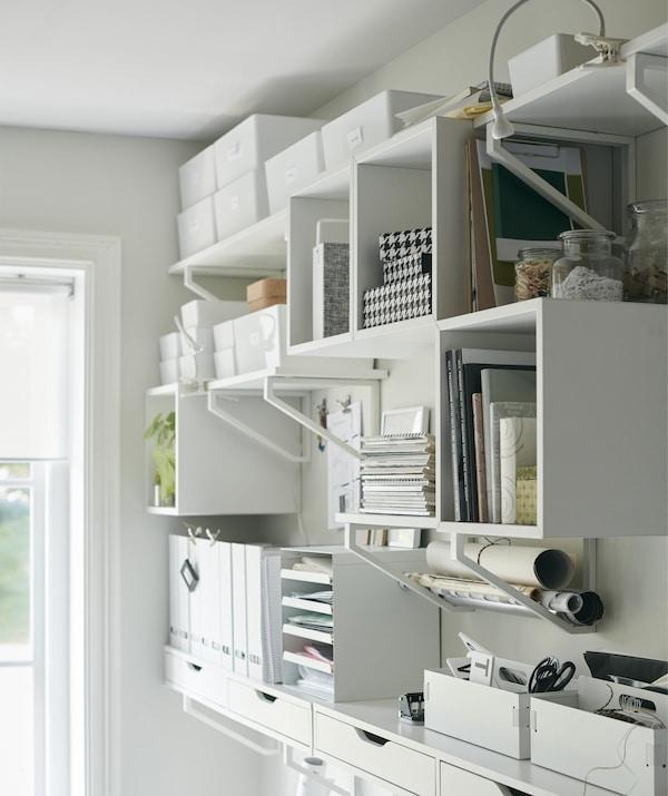 Eine Wand mit Regalen und Boxen, in denen Büroutensilien zu sehen sind, u. a. mit einem an die Wand montierten EKET Regalelement in Weiß