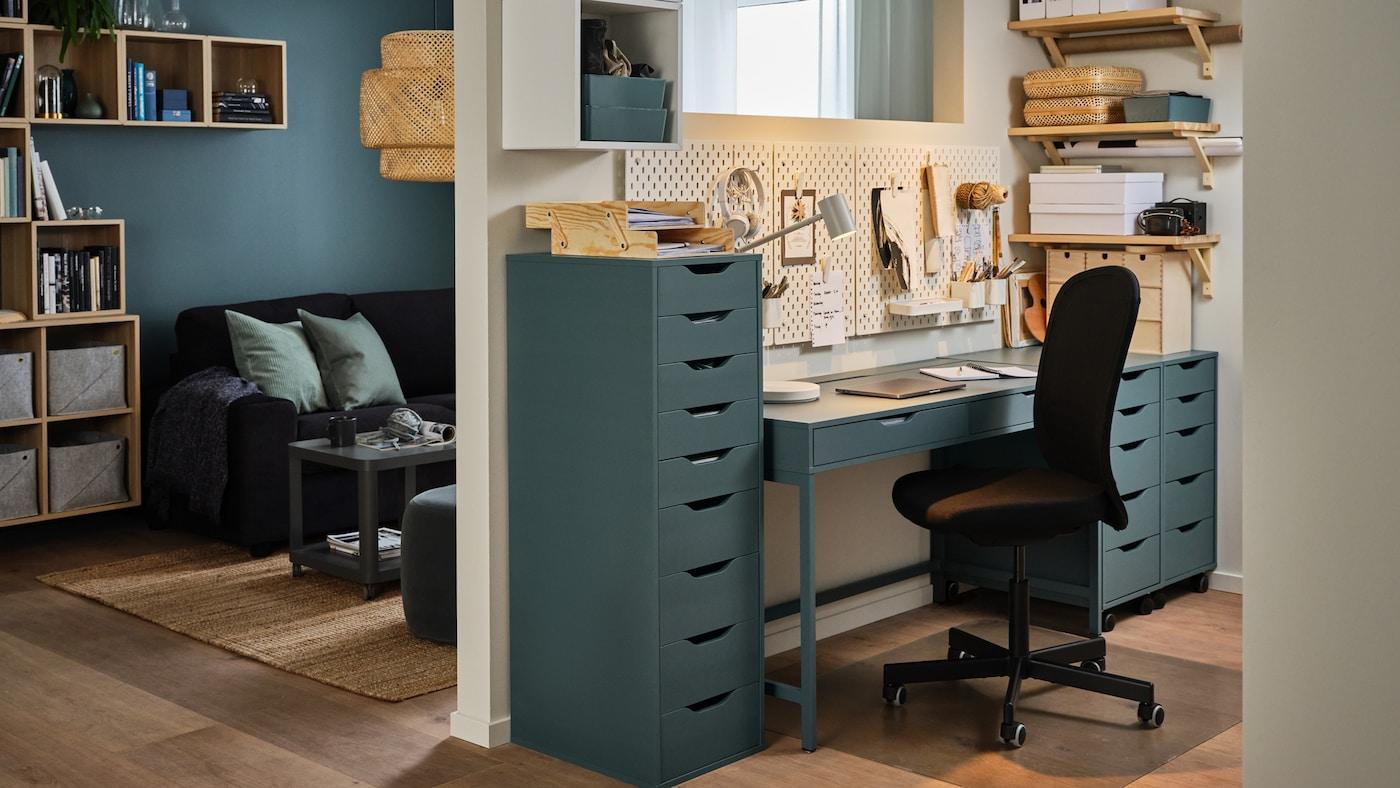 Eine Wand trennt das Wohnzimmer vom Büro zu Hause ab, das aus einem Schreibtisch in Grautürkis, Schubladenelementen und einem schwarzen Drehstuhl besteht.