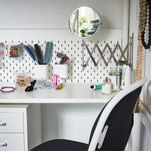 Eine weisse Arbeitsplatte unter einem Hochbett, u. a. mit einem FRÄCK Spiegel an der Wand. Utensilien für Make-up und Frisur finden sich an den Fächern der Lochplatte.