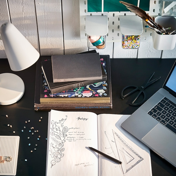 Eine weisse FUBBLA Arbeitsleuchte auf einem schwarzen Schreibtisch.