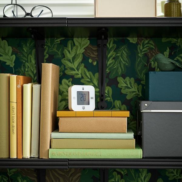 Eine weiße KLOCKIS Uhr/Thermometer/Timer auf einem Stapel Bücher in einem Bücherregal. Auf der Anzeige ist die Zimmertemperatur abzulesen.