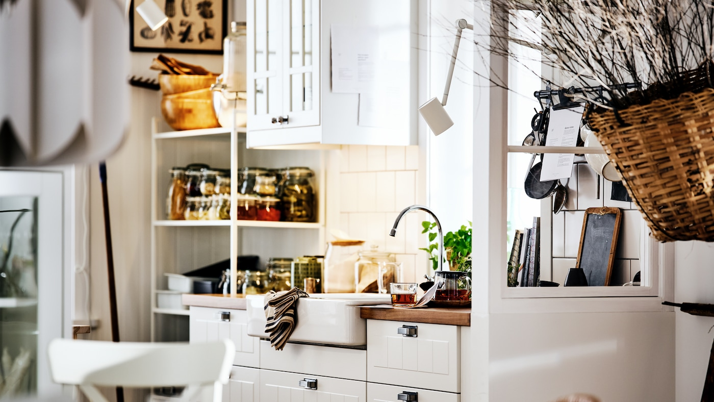 Eine weisse Küche im Landhausstil mit STENSUND Fronten an METOD Schränken, einer weissen Spüle und Regalen mit Dosen und Utensilien.