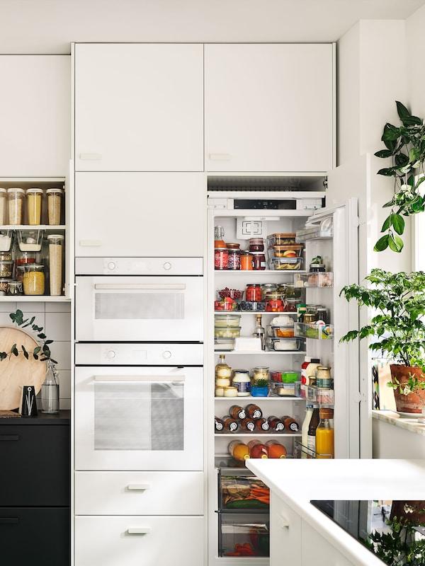 Eine weiße METOD Küche mit offenem Kühlschrank, der viele Aufbewahrungsmöglichkeiten und Ordnung zeigt.