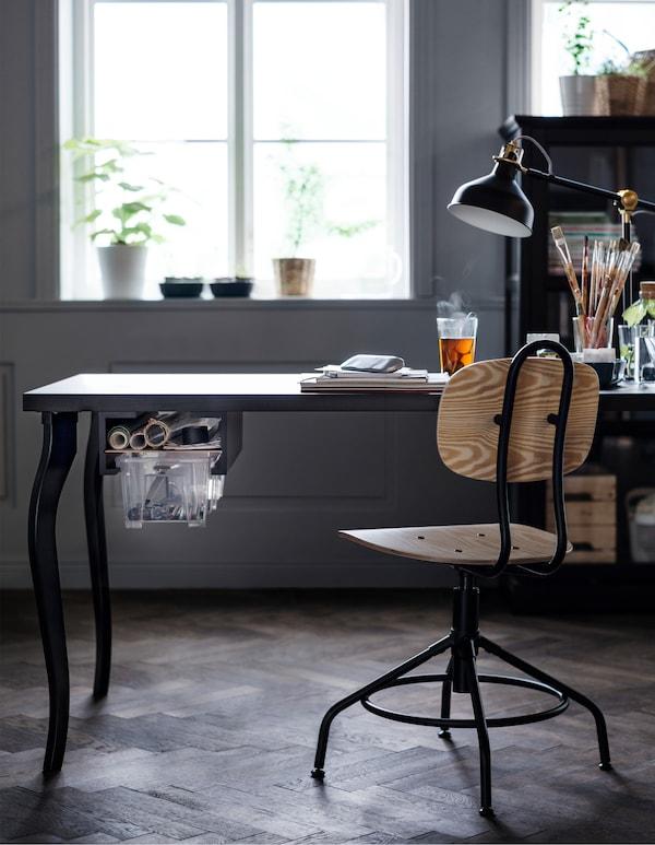 Eine weiße, neutral eingerichtete Küche mit einem großen Küchentisch und Stühlen, darunter zwei MOSSLANDA Bilderleisten in Schwarz als Halterung für transparente Boxen