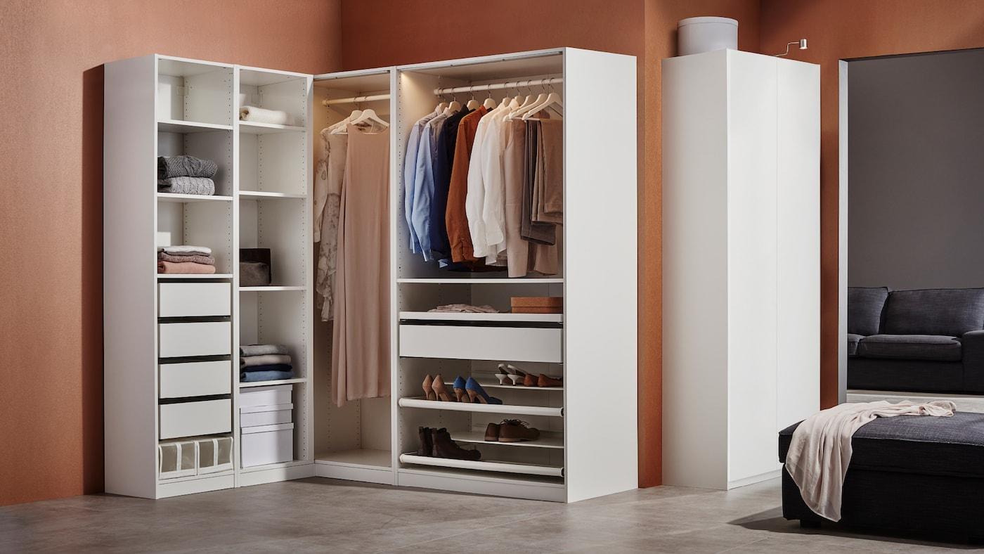 Eine weiße PAX Eckkleiderschrankkombination steht an einer braunen Wand. Sie enthält Schubladen, Boxen, Schuhregale und hängende Kleidung.