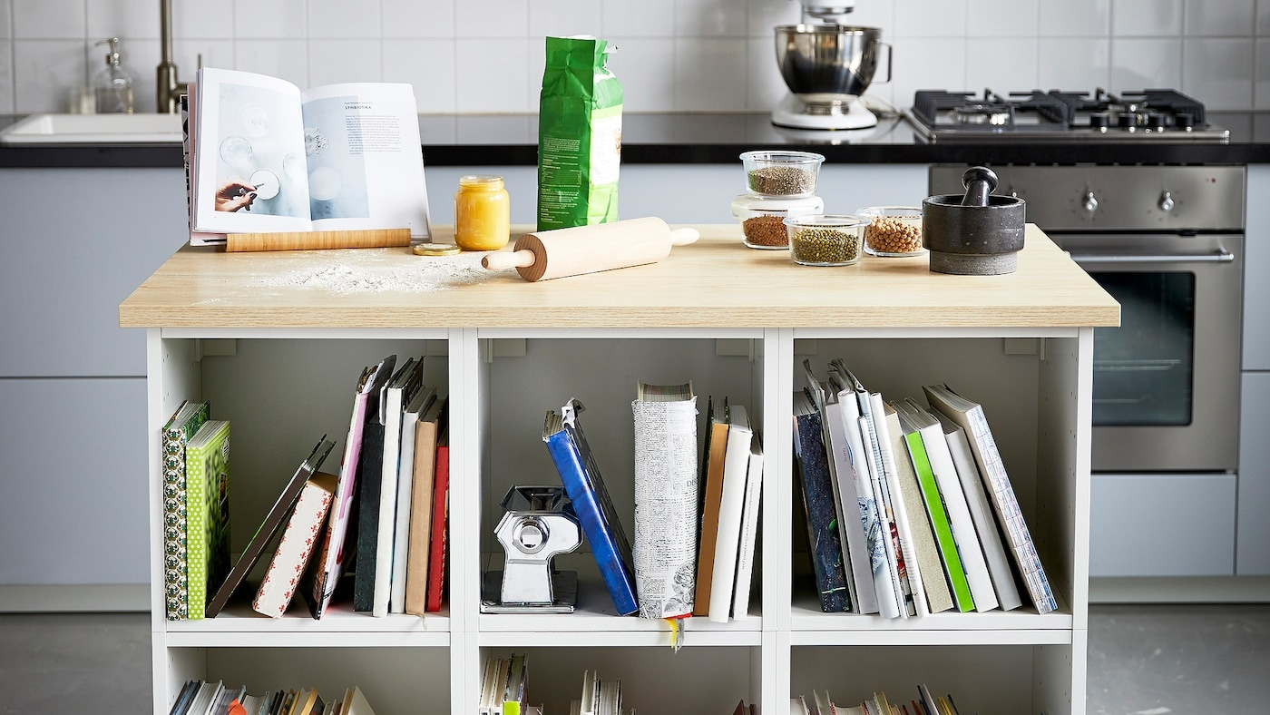 Eine weiße selbstgebaute Kücheninsel mit einer Holzarbeitsplatte mit Backutensilien, Glasbehältern und einem schwarzen Mörser darauf.
