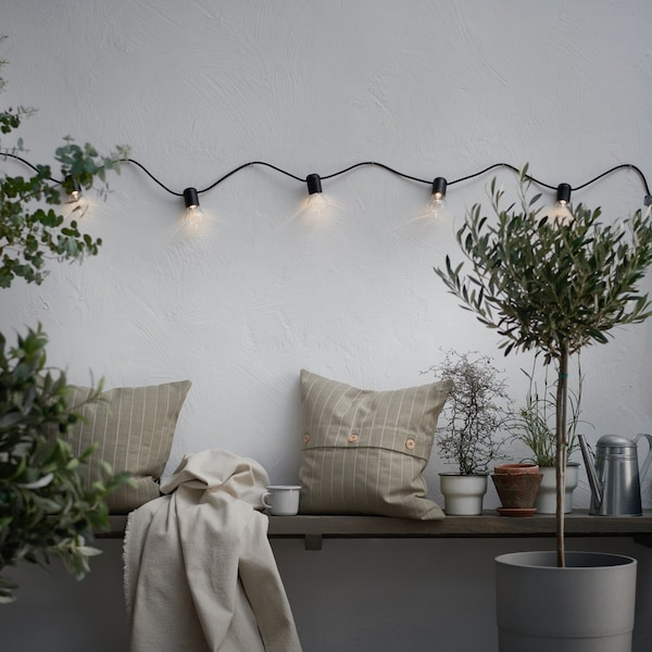 Eine weiße Wand vor der eine Bank steht, ein beiges Kissen liegt auf einer Bank, an der Wand hängt eine Lichterkette, vor der Bank steht ein Olivenbaum