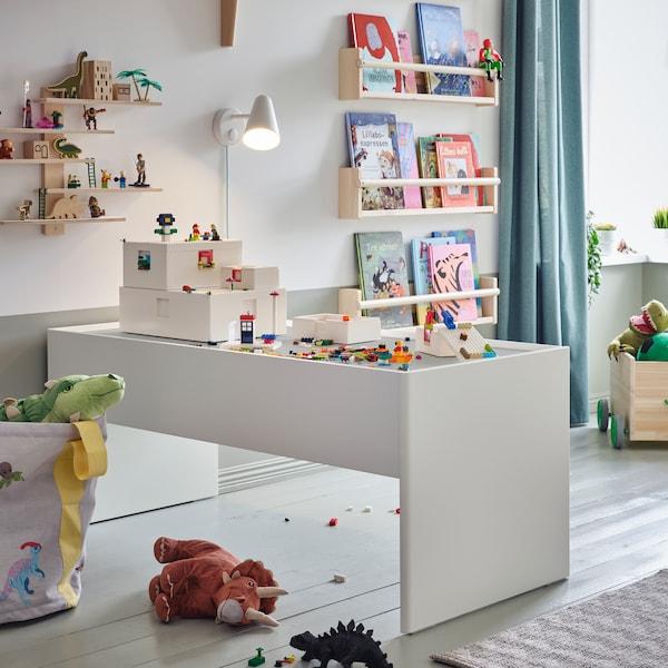 Eine weiße Wandleuchte beleuchtet einen weißen, großzügigen Spieltisch mit Stauraum. BYGGLEK LEGO®-Steine und -Schachteln befinden sich auf der Tischplatte.