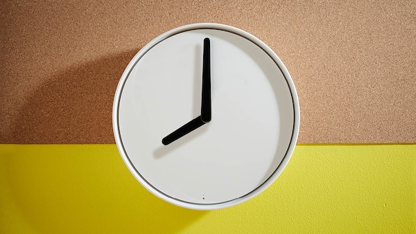 Eine wiesse Wanduhr zeigt 8 Uhr