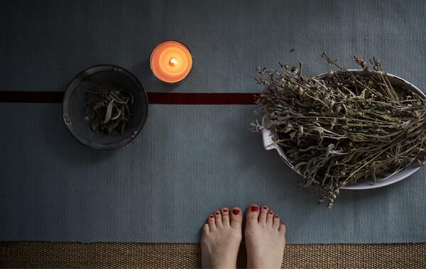 Eine Yogamatte, SINNLIG Duftkerze im Glas Rote Gartenbeeren/rot und eine Schüssel mit Kräutern