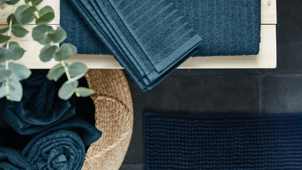 Einige dunkelblaue VÅGSJÖN Handtücher von oben gesehen liegend auf einer hölzernen Sitzbank und aufgerollt in einem FLÅDIS Korb.