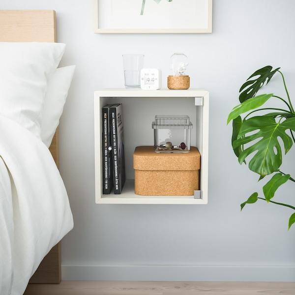 eket bovenkast met glazen deurtje, gevuld met accessoires naast bed