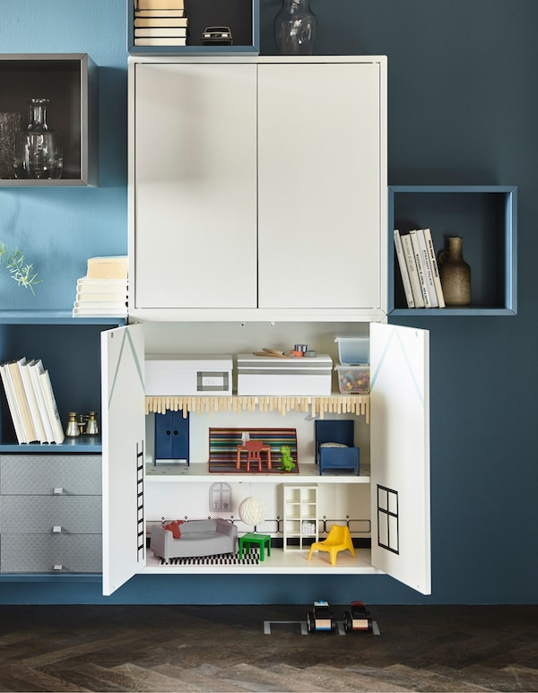 EKET cabinets mounted on the wall of a sophisticated living room are open to reveal the interior is a doll's house.