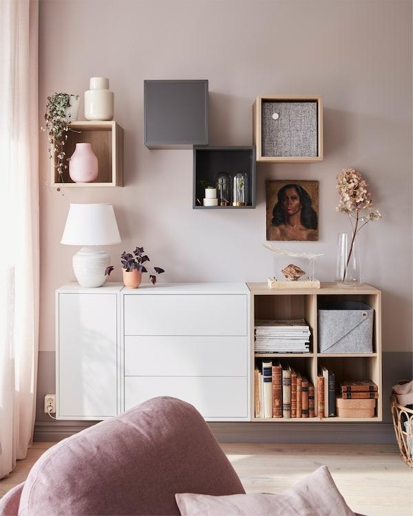 EKET skåp i vitlaserat ekmönster med växter och en lampa placerad på den. Skåpet står i ett vardagsrum med en vilfåtölj.
