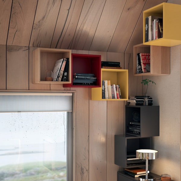 EKET wall-mounted shelving units in various colours, above a lamp on a table and a window with a panoramic, outdoors view.