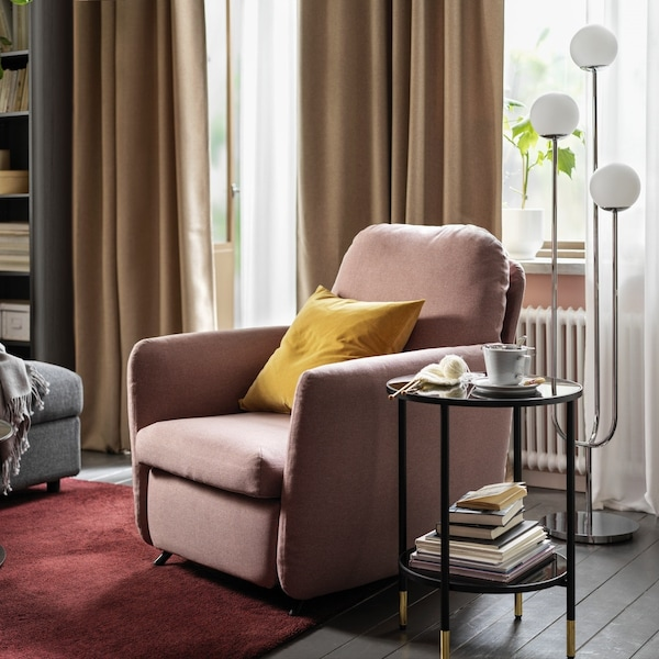 EKOLSUND chair in pink with a yellow pillow.