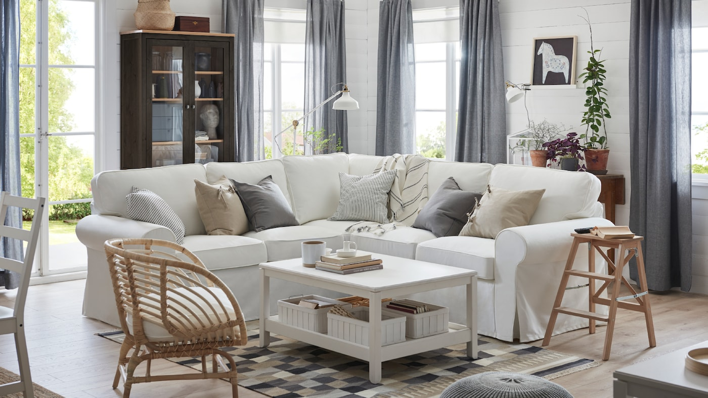 EKTORP, four-seat sectional corner sofa in white, behind a white HAVSTA coffee table in a bright living room setting.