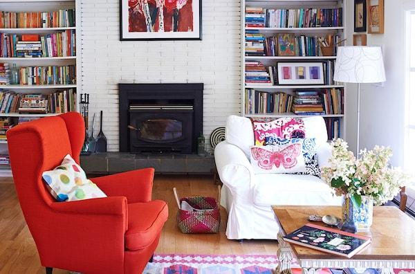 El brillante sillón rojo constituye un punto focal en este luminoso salón con suelos de madera natural y un distintivo estilo rústico.