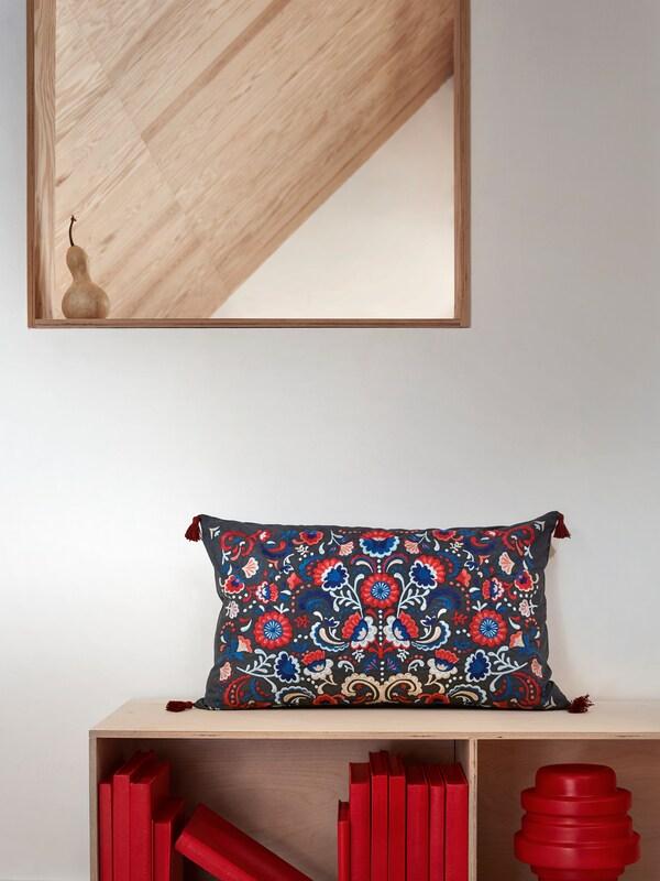El coixí SKOGSKORN presenta un brodat floral d'estil tradicional i borles a les puntes.