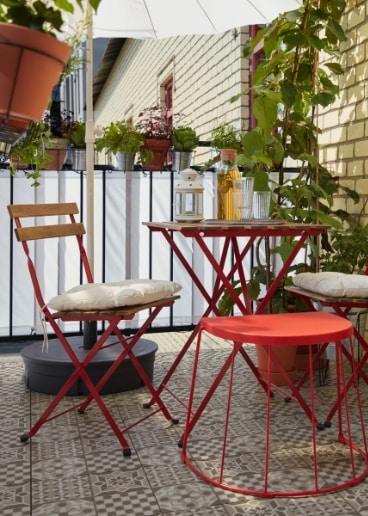 El taburete/mesa auxiliar TRANARÖ en rojo, al lado de una mesa y sillas TÄRNÖ, ofrece asientos adicionales para los invitados.