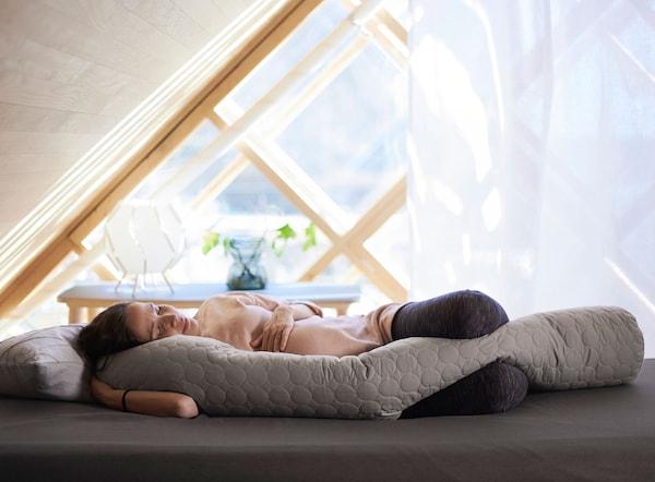 El versátil cojín para cuerpo mostrado como un excelente apoyo para una mujer embarazada tumbada en una cama.