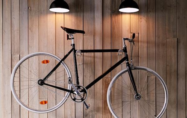 Elegante bici da città appesa alla parete del soggiorno e illuminata dall'alto con delle lampade da parete - IKEA