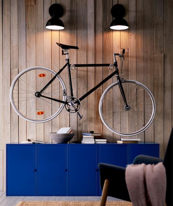 Elegante bici da città appesa sopra i mobili del soggiorno e illuminata dall'alto con delle lampade da parete - IKEA