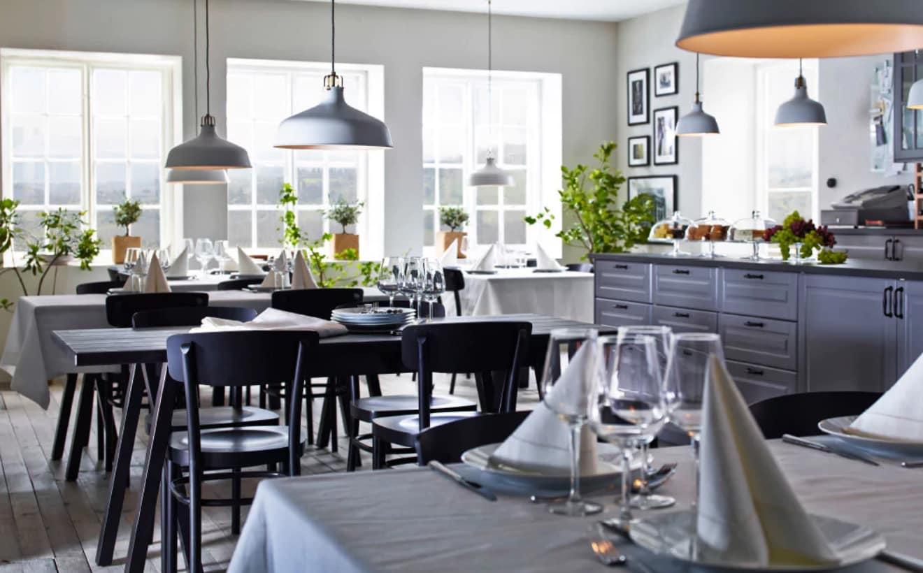 Elegantes Restaurant mit schwarzen GREBBESTAD/RYGGESTAD Tischen, GULLMAJ Tischdecke, Servietten & Weingläsern
