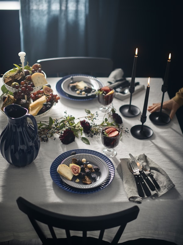 Elegantly set table, including a VANLIGEN jug and LIVNÄRA cutlery, on a white tablecloth in an otherwise dark-colored room.