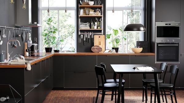 Elegantní kuchyň s policemi KUNGSFORS na upevňovací listě a uzavřenými zásuvkami KUNGSBACKA v antracitové barvě.