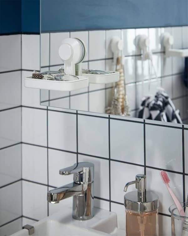 Element s ogledalom, bijela posudica za sapun s vakuumskim držačima, kromirana miješalica za vodu i kromirani dozator sapuna.