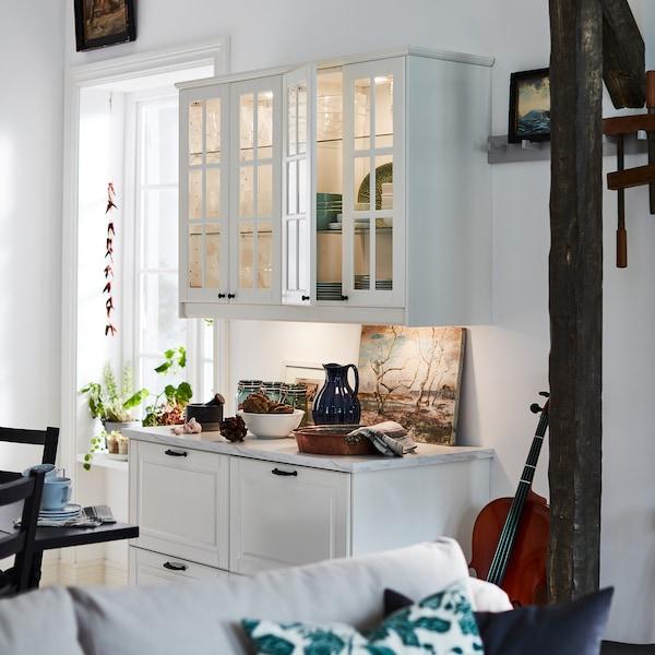 Éléments bas BODBYN en finition blanc cassé avec tiroirs et éléments muraux avec portes vitrées et éclairage intégré sur un pan de mur étroit.