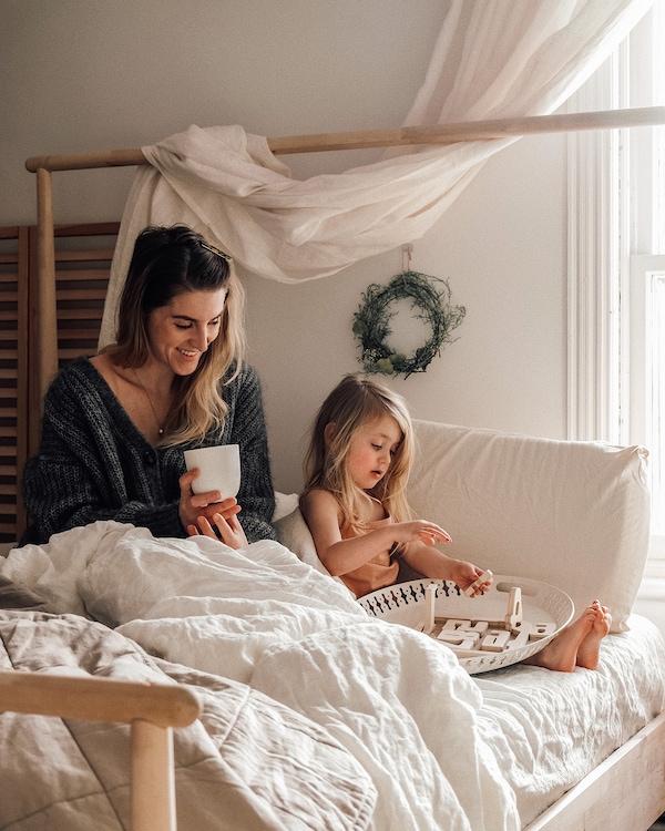 Emilie et sa fille Brook assises sur un lit de bouleau GJÖRA avec draps blancs ondulés.