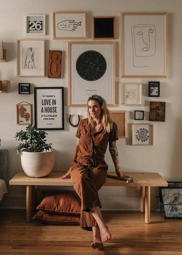 Emilie, la créatrice de contenu et styliste, assise sur un banc devant un mur de galerie dans son appartement.