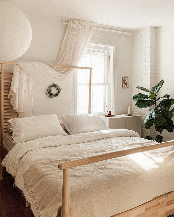 Emilie's bedroom with sunlight filtering through the window, featuring the GJÖRA birch bed, dressed with neutral bedlinens.