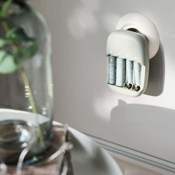 Empat bateri LADDA boleh cas semula di dalam pengecas bateri STENKOL dipasang ke dalam soket pada dinding berwarna putih.