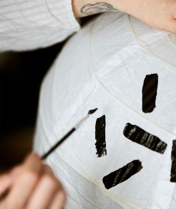 En arm med en tatuerad handled håller en vit papperslampskärm stadig medan ett mönster med svarta linjer målas på den.