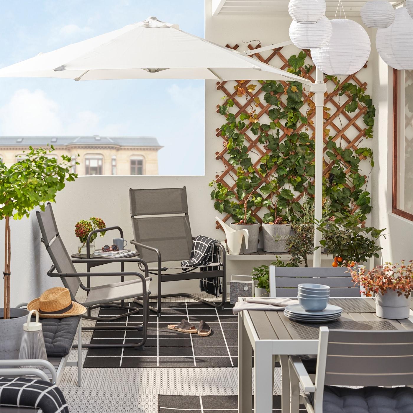 En balkong med HUSARÖ lenestoler og bord, en hvit parasoll, et spisebord og stoler i grått og tepper i svart-hvitt.