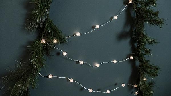 En barrfri julgran i form av SMYCKA konstgjord girlang uppspikad på en vägg och formad som en gran. Granen är klädd med SNÖRYRA ljusslinga.