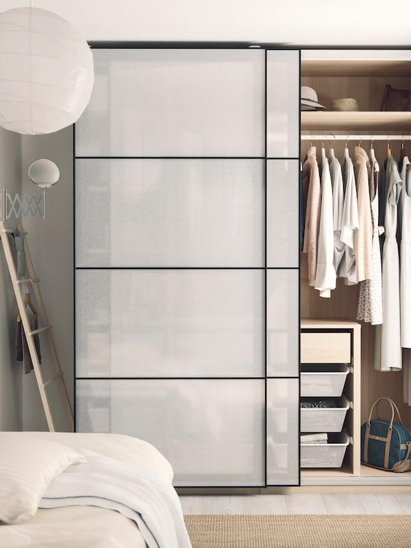 En bild på en garderob med genomskinliga skjutdörrar i ett ljust Sovrum.