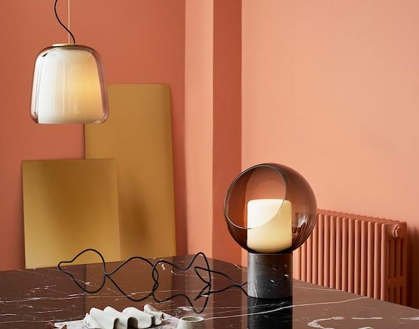 En bordlampe og en loftlampe i gråt glas i et koralfarvet rum.
