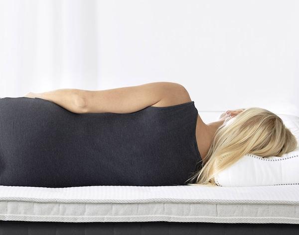 En boxmadras med topmadras på en hvid sengebund med opbevaring.