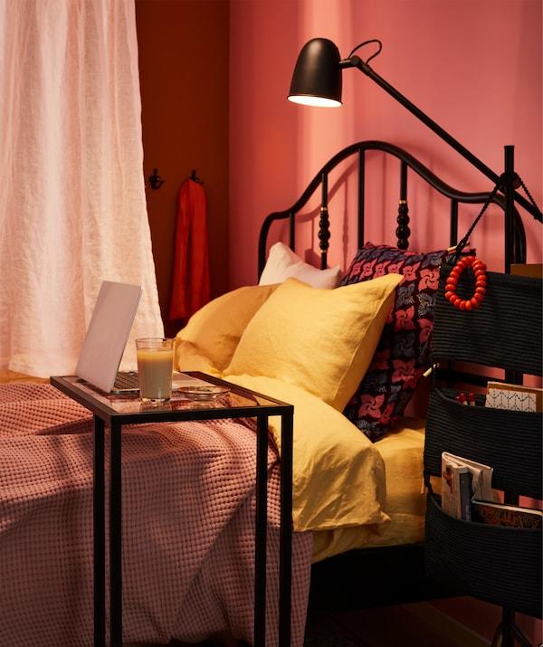 En bred seng er delt på midten med et gardin, der hænger lige over den, og den ene side af sengen er brugt som arbejdsplads.