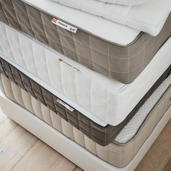 En bunke madrasser i forskellige farver ligger ovenpå hinanden på et trægulv.